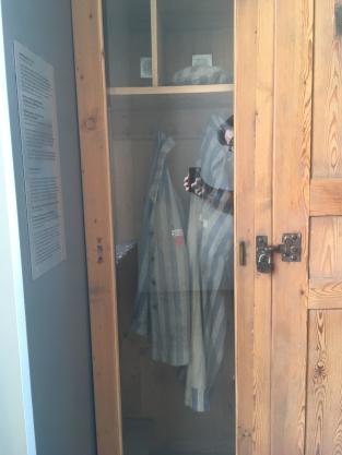 The uniform of an unknown Dachau prisoner hangs on display
